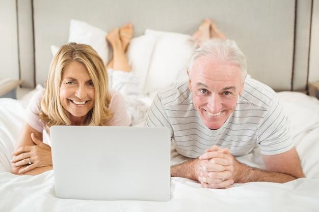 ベッドに横になっているとラップトップを使用して笑顔のカップルの肖像画