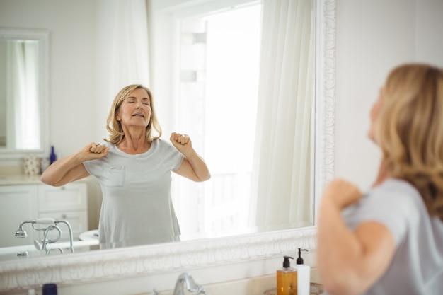 年配の女性が鏡の前でストレッチ