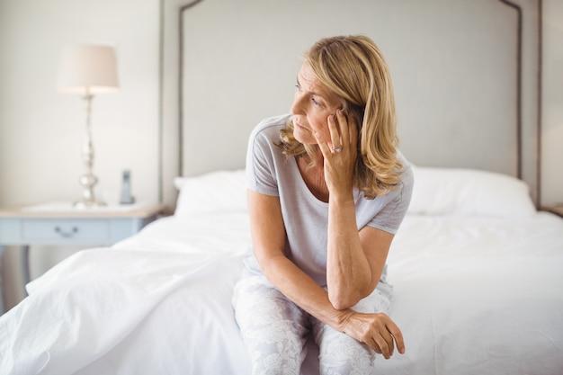 寝室のベッドの上に座って緊張した女性