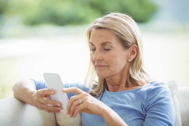 リビングルームで携帯電話を使用して年配の女性