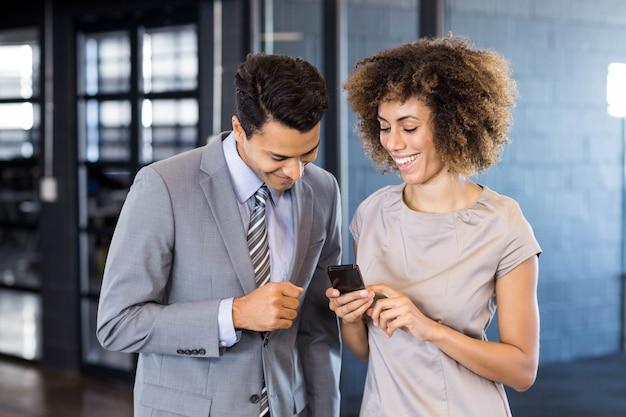 ビジネスマンのオフィスで携帯電話を保持している若い女性に話しています。