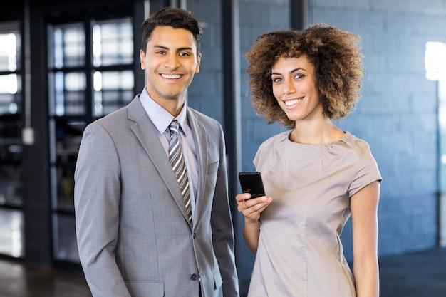 ビジネスの男性のオフィスで携帯電話を保持している若い女性と一緒に立っています。