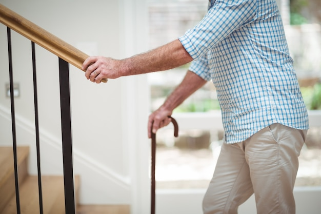 Старший мужчина, поднимаясь наверх с тростью