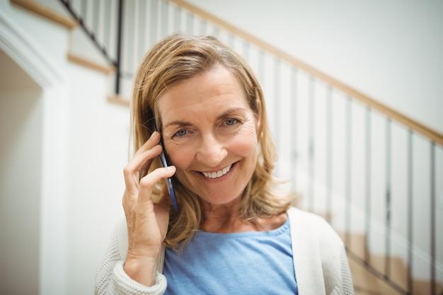 Улыбается старший женщина разговаривает по мобильному телефону