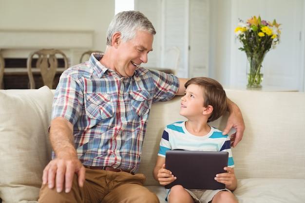 Дед с внуком с помощью цифрового планшета на диване