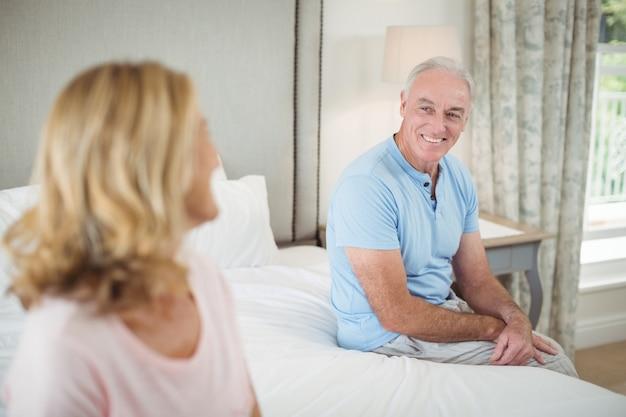 寝室で互いに対話する年配のカップル