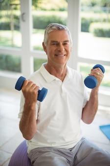 Старший мужчина упражнения с гантелями на дому