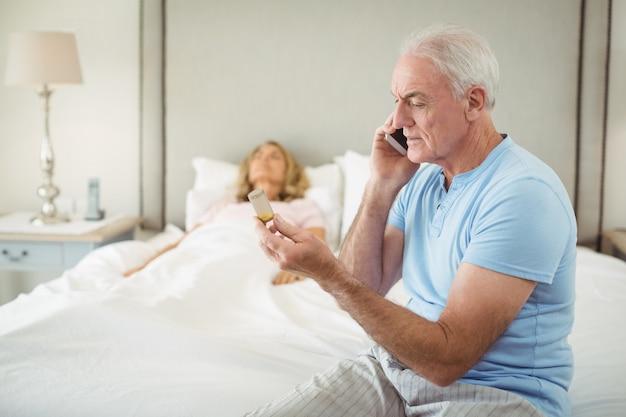 年配の女性が寝室で休んでいる間携帯電話で話している年配の男性