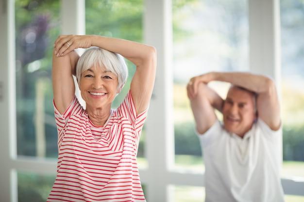 Пожилая пара выполняет упражнения на растяжку дома