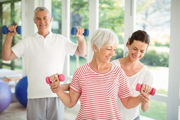 運動をすることで年配のカップルを支援する女性のトレーナー