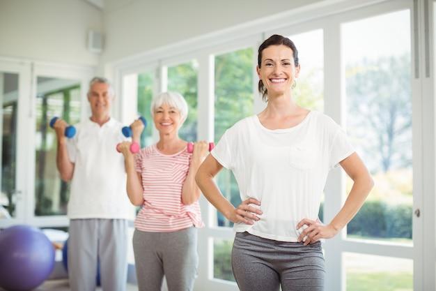 ダンベルで運動しながら年配のカップルと立っている女性のトレーナーの肖像画