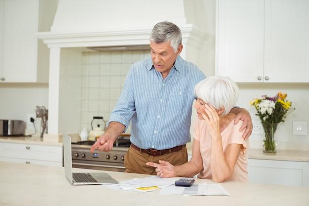 年配の男性が台所で年配の女性との相互作用