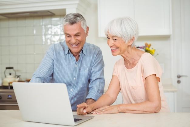 台所でラップトップを使用して年配のカップル