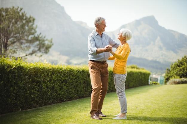 Пожилая пара танцует в парке