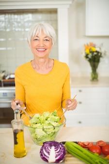 Старшая женщина готовит овощной салат