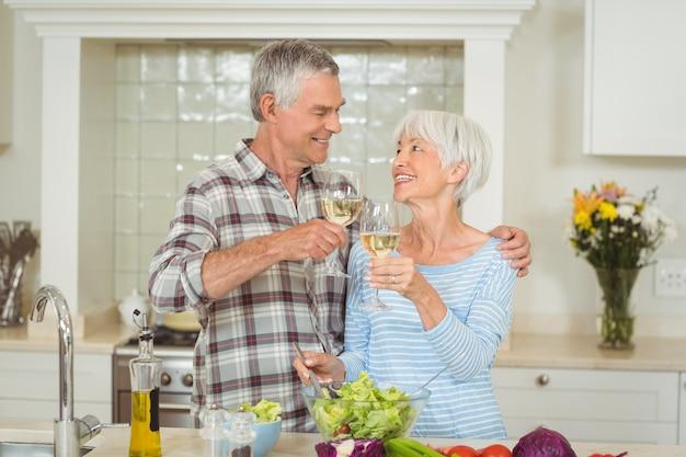 Пожилая пара поджаривания бокалов вина