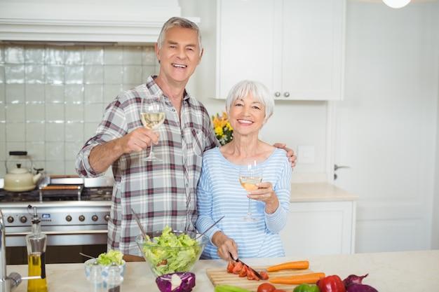 ワインのグラスを保持している年配のカップル