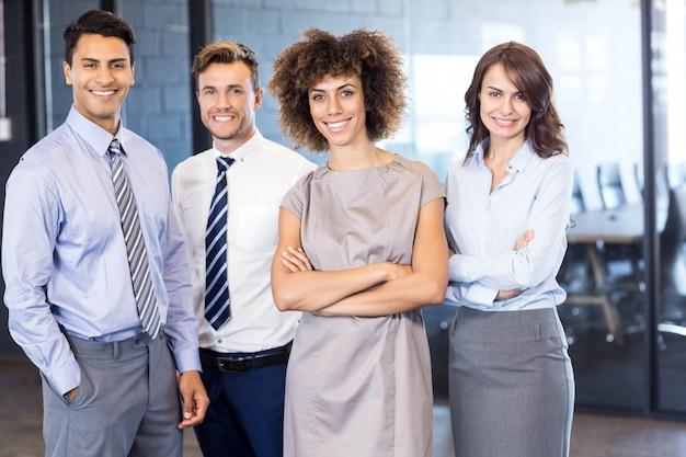 彼らの手を組んでオフィスに立っている自信を持ってビジネスチームの肖像画