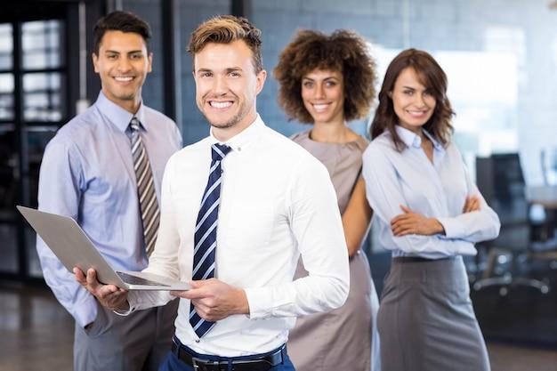 彼のチームがオフィスで彼の後ろに立っている間ビジネスマンのラップトップで立っています。