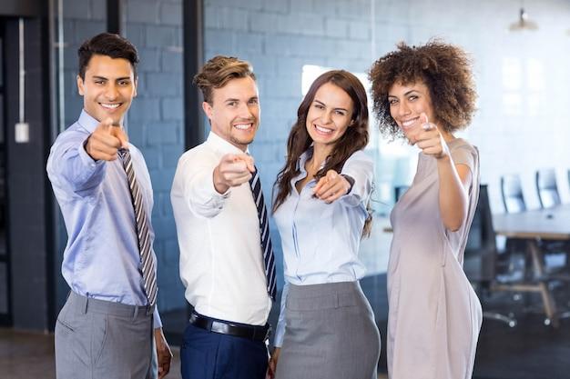 自信を持って事業チームの笑みを浮かべて、オフィスで自分の指を前方に向けるの肖像画