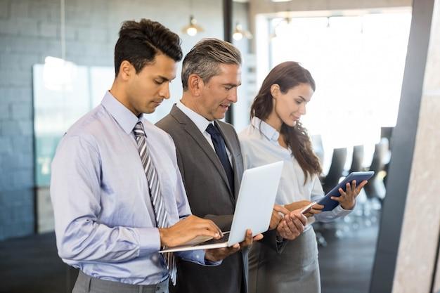 Деловые люди стоят в ряд и используют мобильный телефон, ноутбук и цифровой планшет в офисе