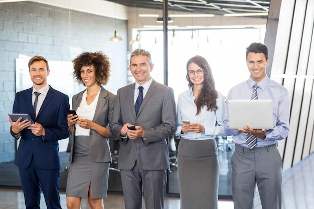Деловые люди, стоящие в ряд и использующие мобильный телефон, ноутбук и цифровой планшет в офисе