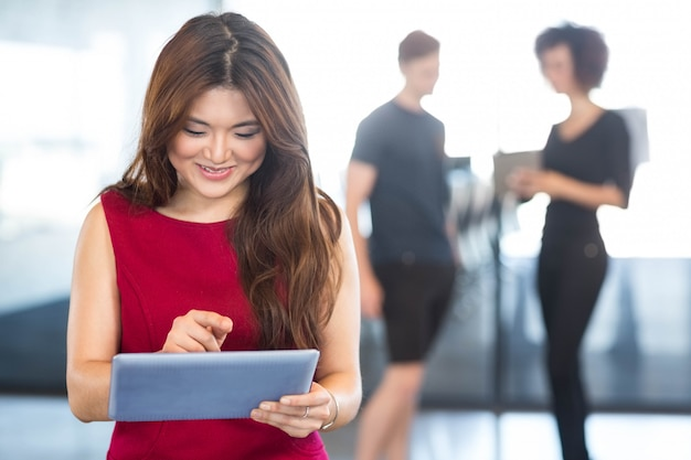 Красивая молодая женщина с использованием цифрового планшета в офисе