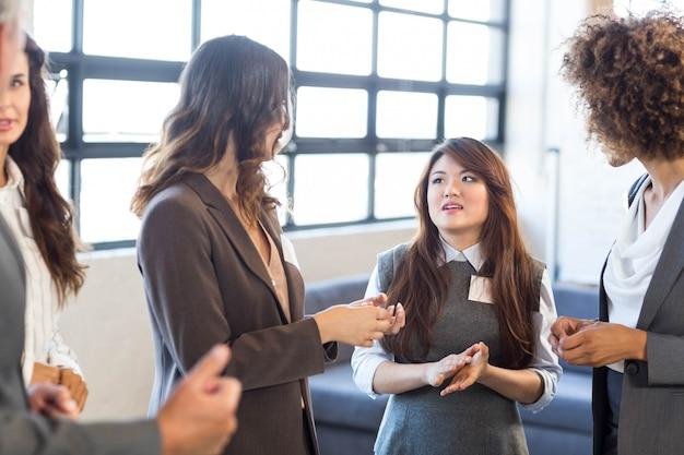 Бизнес-команда, стоящая вместе и взаимодействующая в офисе