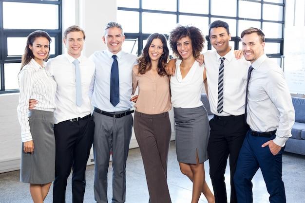 一緒に立っているとオフィスで笑顔のビジネス人々の肖像画