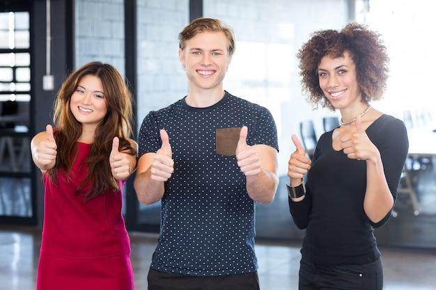Портрет руководителей предприятий, давая пальцы вверх и улыбается в офисе