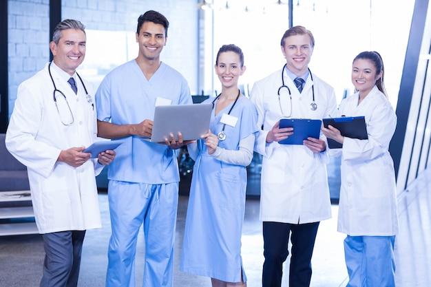 Портрет доктора с цифровым планшетом, ноутбуком и медицинским заключением