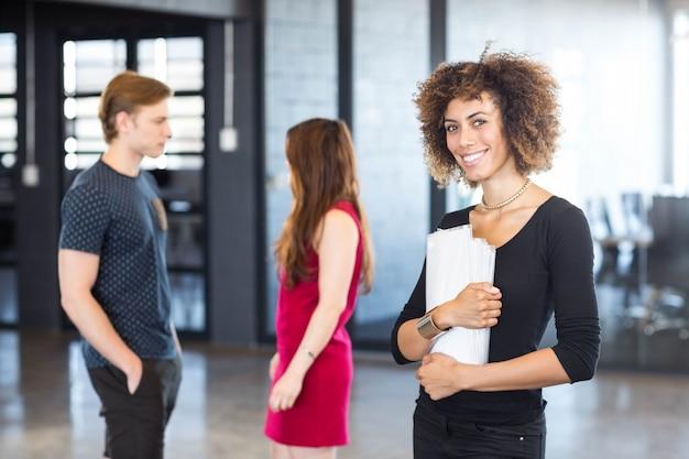 Портрет руководителя бизнеса держа задание бумаги и улыбаясь в офисе