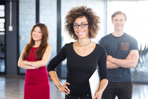 Портрет улыбающихся коллег, стоя в офисе
