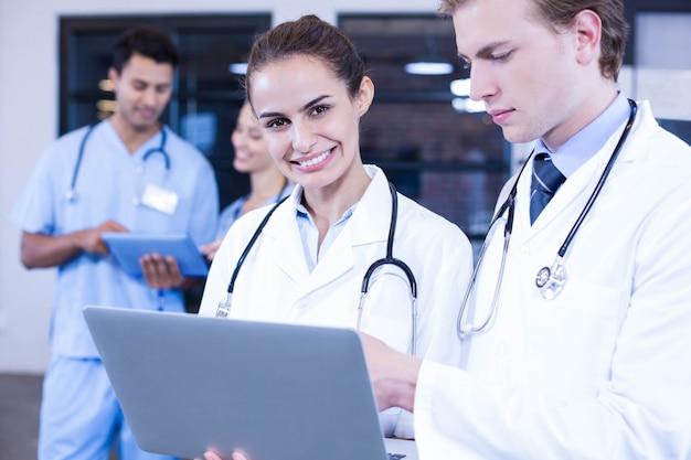 ラップトップを使用して、彼女の同僚が後ろで議論している間に笑顔の医者