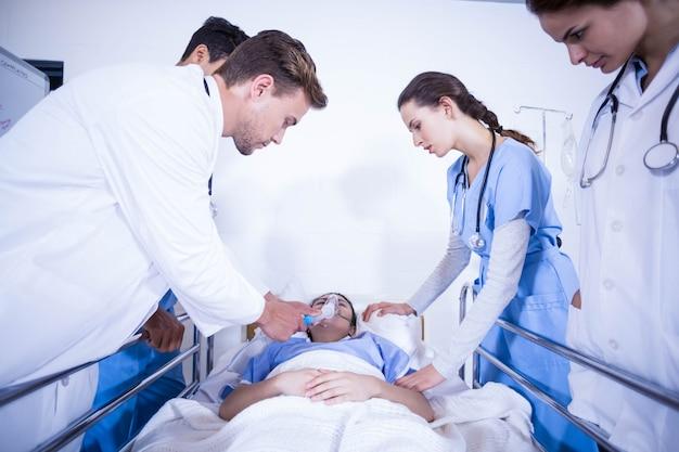 医師が病院でベッドの上で患者を調べる