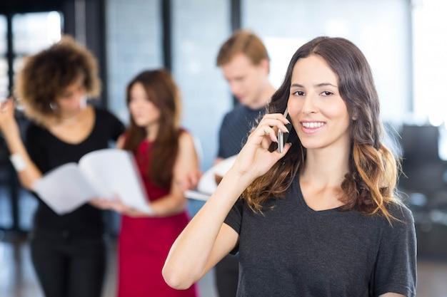 Портрет бизнесвумен, говорить на мобильном телефоне, а ее коллеги, стоя за ней в офисе