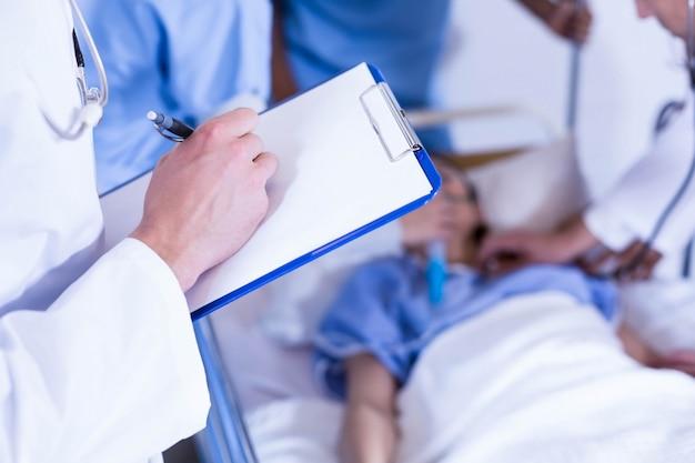 クリップボードに書き込む医師や病院で後ろに患者を調べる他の医師