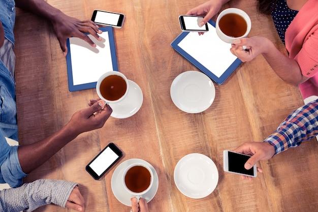 Коллеги, использующие технологии на столе, держа кофейные чашки в офисе
