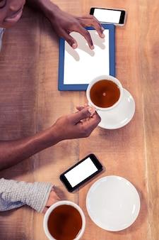 Коллеги, держащие кофейные чашки, используя технологии на столе, находясь в офисе
