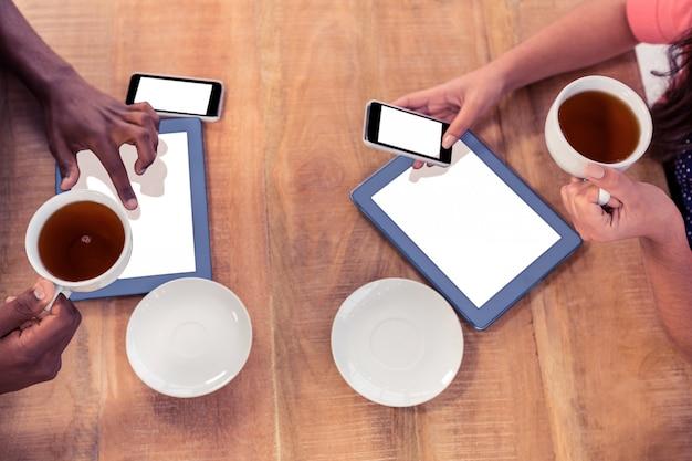 Коллеги держат кофейные чашки, используя технологии на столе в креативном офисе