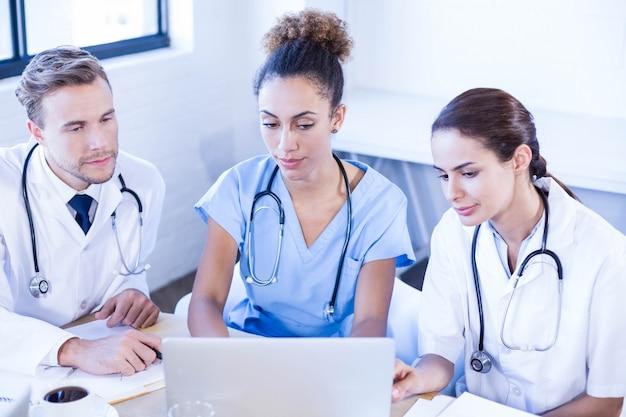 Медицинская группа смотрит в ноутбук и проводит обсуждение в конференц-зале