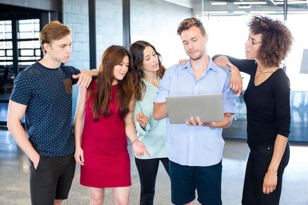 Коллеги обсуждают в ноутбуке в офисе