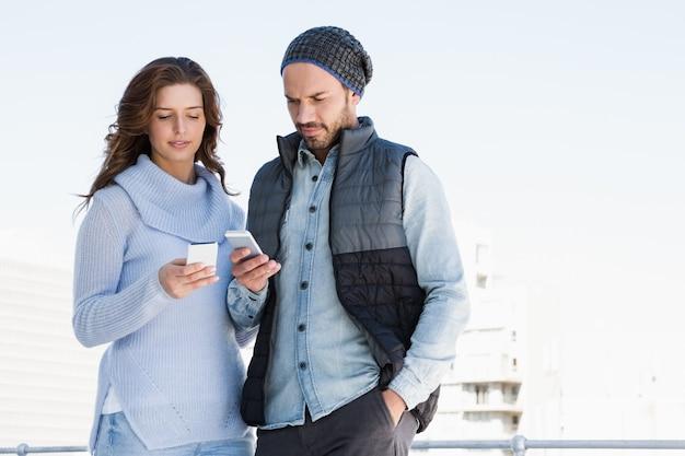 屋外で携帯電話を使用して若いカップル