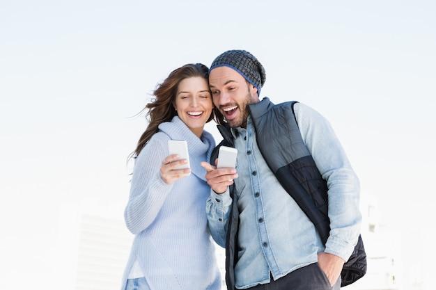 屋外で携帯電話を使用して幸せな若いカップル