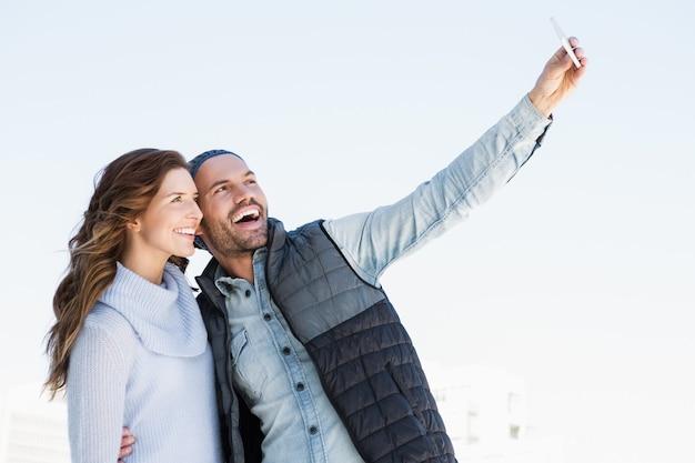 Молодая счастливая пара, делающая селфи на мобильном телефоне на открытом воздухе