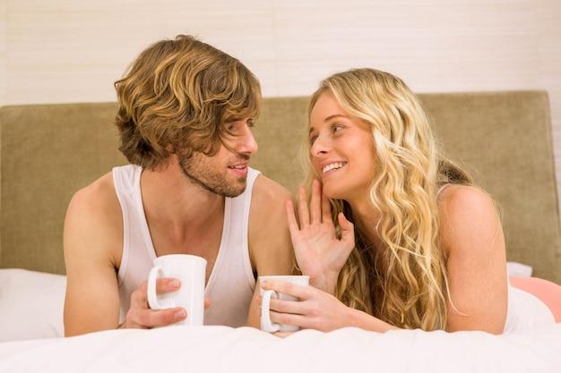 Милая пара пьет кофе в своей постели в спальне