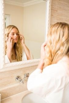 バスルームの鏡で自分自身を見ているきれいな女性