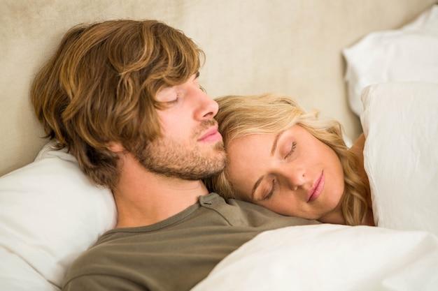 Милая пара спит на кровати в спальне