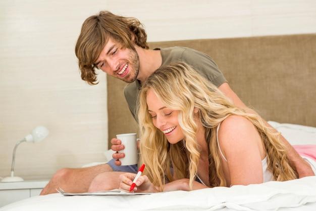 Красивый мужчина пьет кофе, а подруга пишет на их кровати