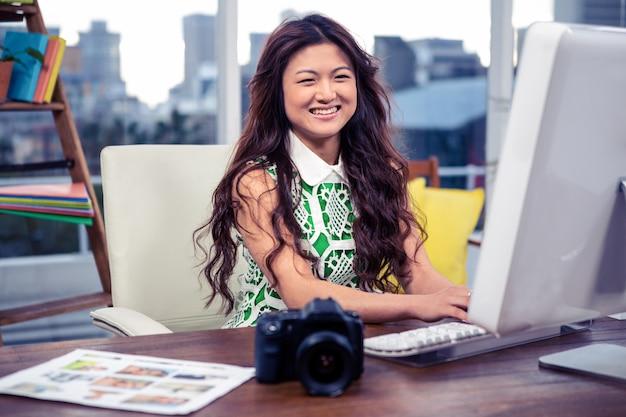 オフィスのコンピューターを使用して笑顔の創造的な実業家